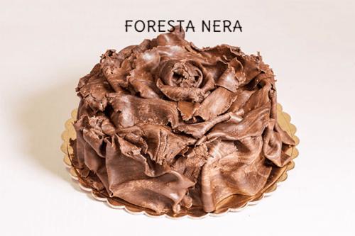 FORESTA NERA - Base di pan di spagna al cioccolato con farcitura di panna-cioccolato e amarena in pezzi. Esternamente decorata con una pasta al cioccolato